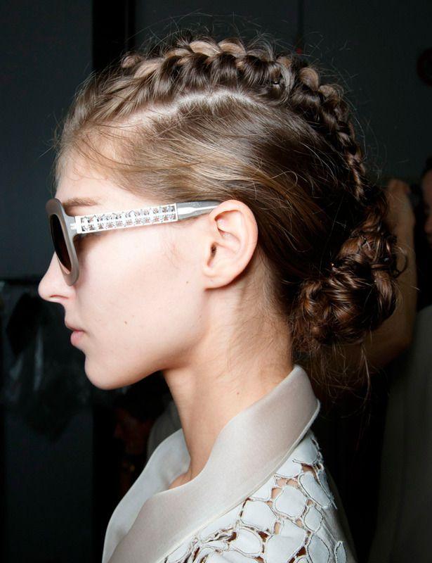 Dos trenzas pegadas a la cabeza se unen en un moño en el look propuesto por Giorgio Armani.