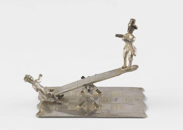 Anthonie Hellegers | Kinderen op wip, Anthonie Hellegers, c. 1844 - c. 1867 | Op een langwerpige plaat staat een wip. Op de wip zit aan de ene kant een man en aan de andere kant staat een man. De korte zijde van de plaat is geschulpt. In de plaat is een ruitpatroon gegraveerd. Het beeld is gemerkt: mt.= A. Hellegers en een geschreven S.