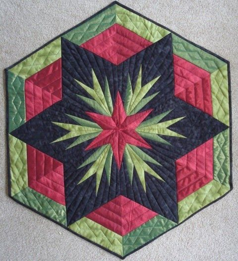 """This is my latest invention called """"Cactus Rose"""". The center of the wall quilt is paper pieced. Notice the shinny fabric in the dark gree..."""