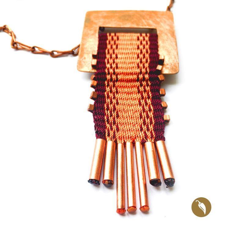 Collardonde el protagonista absoluto es una pieza tejida a telar. Gabriela Casteránrescata estatécnica para honrar nuestros orígenes.El brillo del metal se contrapone a la calidez de las fibras de tono violeta en los que sedistingue un diseño central. En los bordes laterales de la pieza se distiguen cuentas de cobre que combinan con las piezas finales, que como flecos en vuelven las últimas hebras de la urdiembre. El collar es parte de la colecciónNahuenque alude al fonema…
