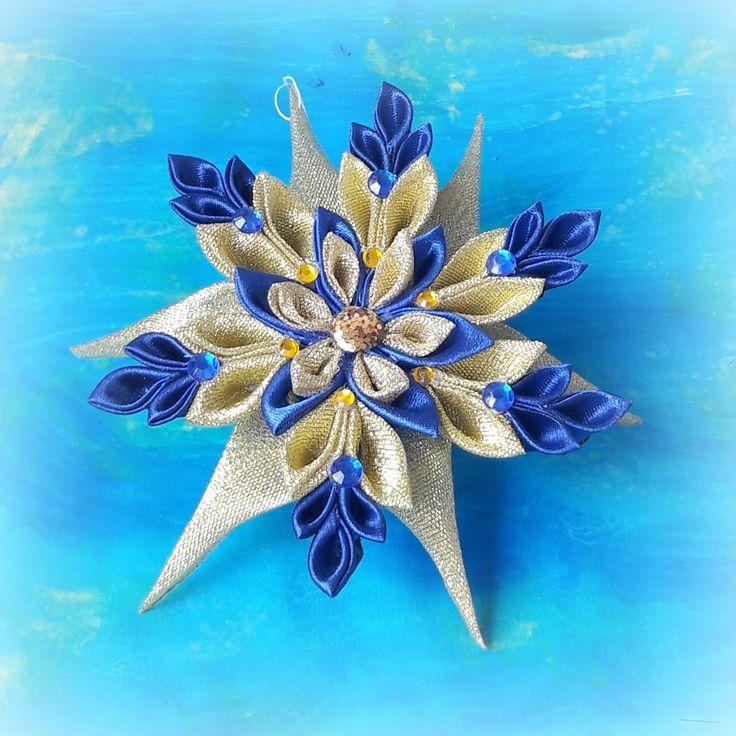 Medea+-+vločka+Sněhová+vločka+vyrobená+technikou+kanzashi+ze+saténových+stuh.+Tato+vločka+je+kombinací+tmavě+modré+a+zlaté.+Dozdobena+je+dekorativními+kamínky.+Průměr+vločky+je+14cm.+Cena+za+1kus!+>