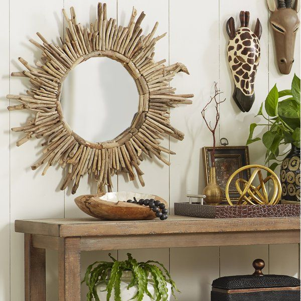 Brimming with coastal flair, this statement-making wall mirror pairs driftwood details with a sunburst design for a look that draws the eye to your well-curated ensemble. Its natural hues pair perfectly with warm wood furniture and a breezy arrangement of potted ferns, while its distinctive silhouette adds an artful touch to any space. Add this wall mirror to the den to complement an eclectic boho aesthetic, then pair it with tapestry wall decor and paisley-pattern pillows for a cohesive…