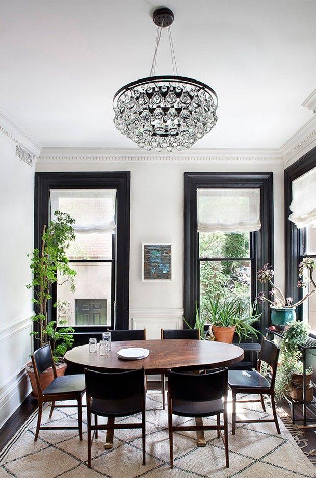 Sala de jantar com janelas generosas, mesa oval de madeira e lustre de cristais