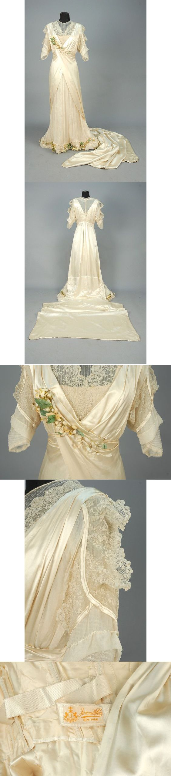 Trained wedding gown with lace and orange blossom trim, 1920s. Ivory charmeuse pleated and wrapped bodice having gauze short sleeve and bodice insert trimmed in needle lace with orange blossom corsage, open skirt over gathered front panel of gauze on silk decorated at hem with a wavy band of self ruffles, silk piping and orange blossoms, long square train. Petersham label: Jennie & Co. New York. B-34, W-24, H-38, Front L-56, back L-69 plus 42 inch train. $360