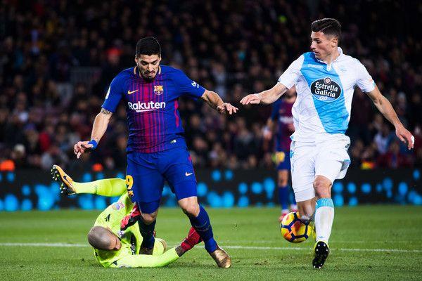 Ruben Martinez of Deportivo La Coruna clears a ball conducted by Luis Suarez of FC Barcelona next to Fabian Schar of Deportivo La Coruna during the La Liga match between FC Barcelona and Deportivo La Coruna at Camp Nou on December 17, 2017 in Barcelona.