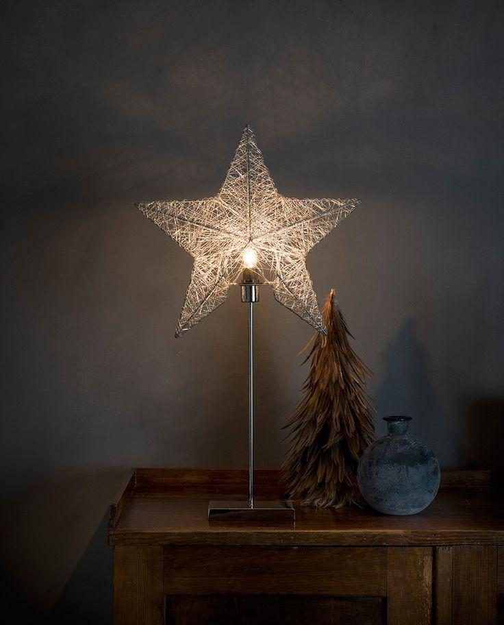 Delikat adventsstjerne på fot i sølv utførelse fra Konstsmide. Metallstjernen har et tredimensjonalt rammeverk som er spunnet med tynn metalltråd. Dette gir stjernen et meget vakkert lysspill.
