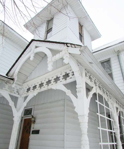 white queen anne exterior with curved porch supports, trusses