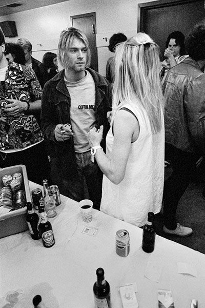 """Backstage at a Seattle Neil Young/Sonic Youth concert, 1991 - """"[Kurt's chatting with] Kim Gordon from Sonic Youth. This was after their set and everyone went up to the dressing room. First we did a lineup photo with the members of Sonic Youth and Nirvana and some contest winners, a posed thing. After that, I was taking candids of people talking. I could tell that Kurt was pretty starstruck talking to Kim [though] I'm sure they'd met before on the road. It was before 'Nevermind' was…"""