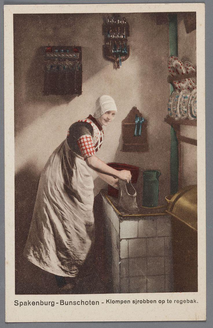 Spakenburg - Bunschoten - Klompen sjrobben op de regebak. Vrouw in interieur bij regenbak. 1910-1920 Een poserende jonge vrouw bij de regenbak. Zij draagt de kanten muts, een lichte kraplap, de ongedeelde rode doek en een wit schort. Aan de kulder rood geruite boormouwtjes. Aan de muur lepelrekjes en borden in een rek. #Utrecht #Spakenburg