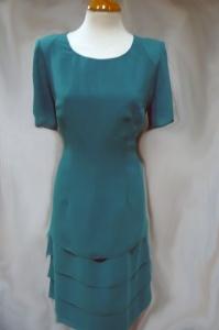Vestido en gasa de poliéster. La falda lleva distintas capas. Manga corta, totalmente forrado, colore lisos en verde jade y negro.