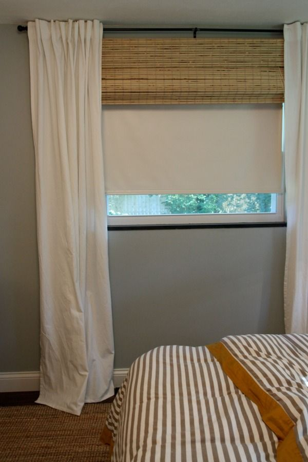 Install roller shade behind bamboo shade. Bamboo shade hides roller shade when not in use.  Black-out shade for room darkening. Layered window treatment idea