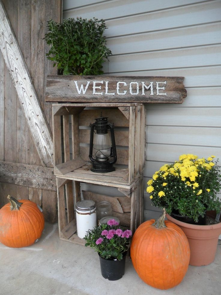 fall decor on farmhouse porch outside the farmhouse
