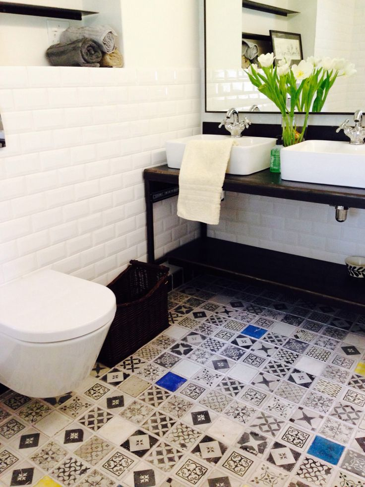 Patterned and hand printed black & white geometric designs on handmade floor tiles in a bathroom and shower.