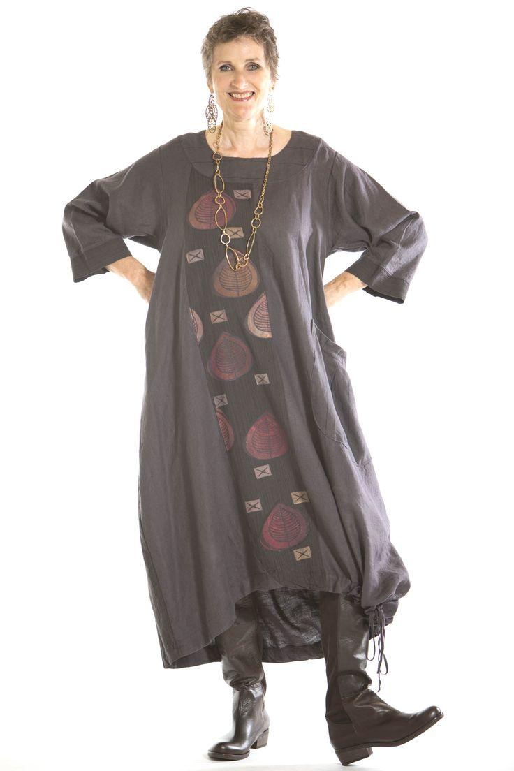 Rechte jurk met brede hals en inzet voorpand van andere stof. Grote opgestikte zak  en zoom met koord om ballonlijn te creëren.