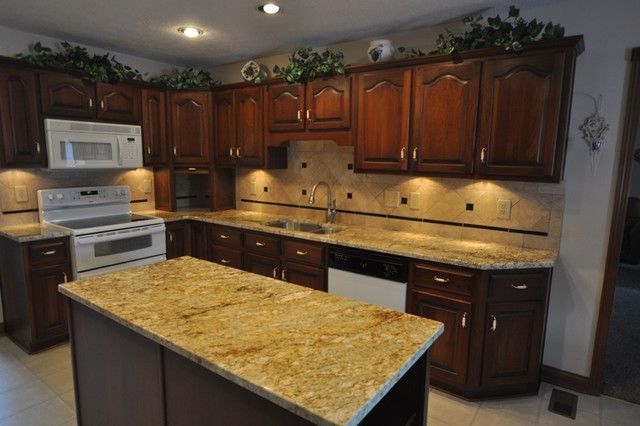 granite countertops with tile backsplash and dark brown cabinets