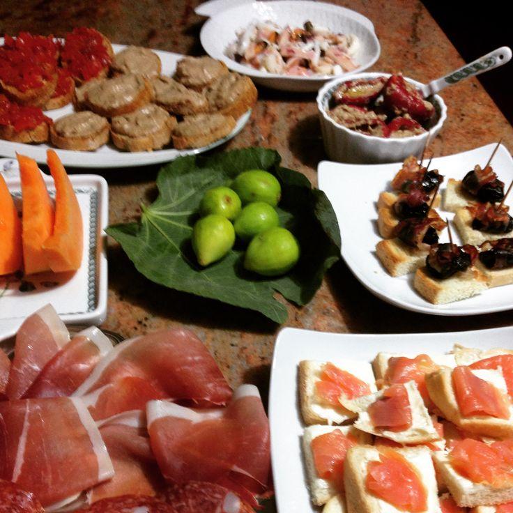 Una cena aperitivo: prosciutto e salame con melone e fichi, crostini ai pomodorini, ai fegatini, al salmone e alle prugne e pancetta, insalata di mare, peperoncini ripieni