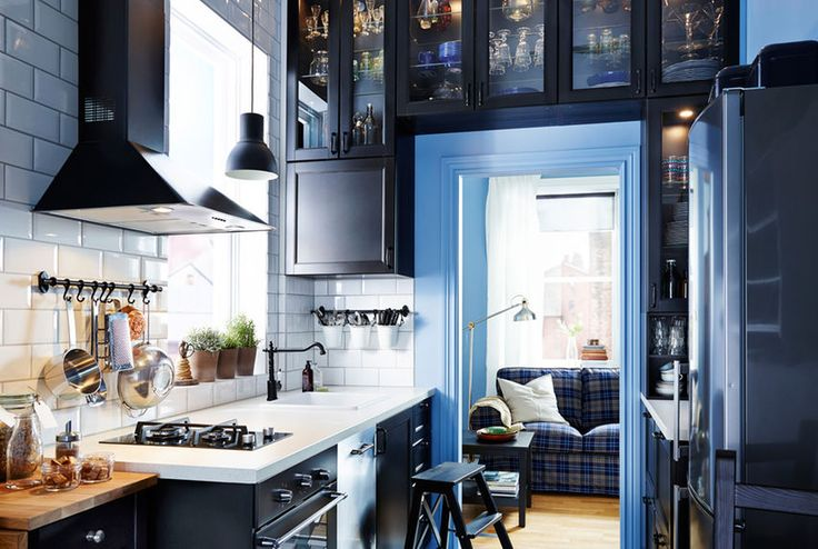 Narrow kitchen with IKEA kitchen cabinets built all around the doorframe.