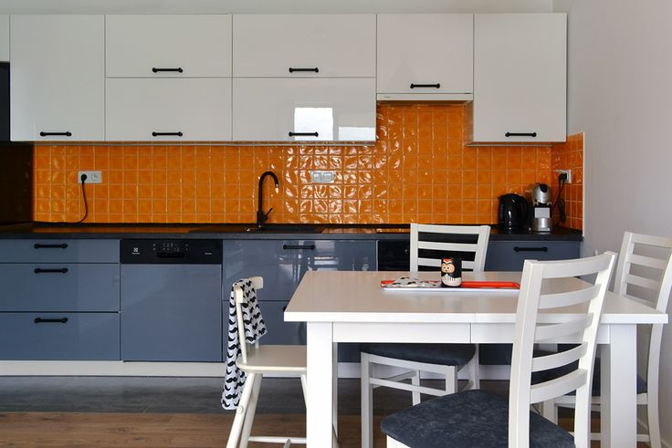 Kuchnia w bieli, szarości i z odrobiną koloru pomarańczowego. Nowoczesna, energetyczna. Idealna dla niejadków, gdyż pomarańczowy pobudza apetyt. Takie było założenie dla tej 4-osobowej rodziny :)