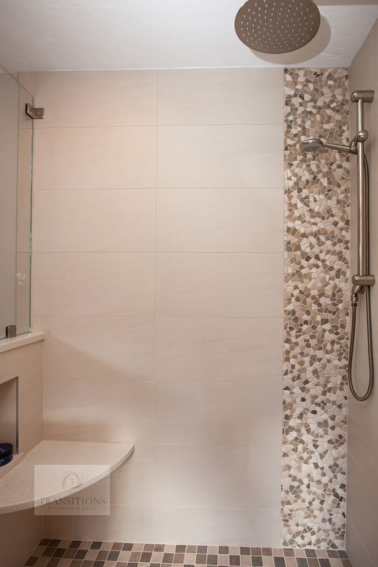This bathroom design offers a comfortable setting, and is part of a master suite including a walk-in closet.  Full of stylish details, the bathroom is separated from the closet by a sliding barn door that adds a rustic touch to the otherwise contemporary style. The large shower incorporates a rainfall and handheld showerhead, mosaic tile details, plus a handy shower niche storage and built-in seat. Photos by Susan Hagstrom