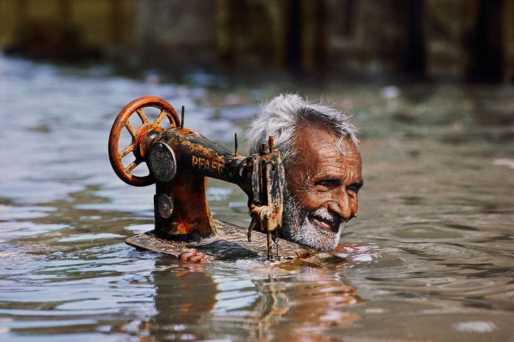 The spirit of India, captured by Steve McCurry – in pictures A tailor carries his sewing machine through monsoon waters, Porbandar, Gujarat, 1983