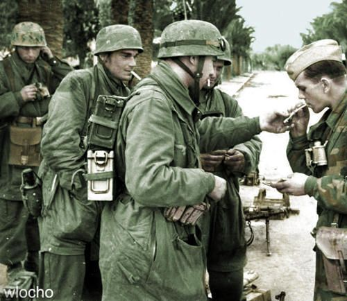 German Fallschirmjäger paratroopers share cigarettes together during a brief moment of downtime following a recent triumph in combat during the German invasion of Greece. Spring, 1941.
