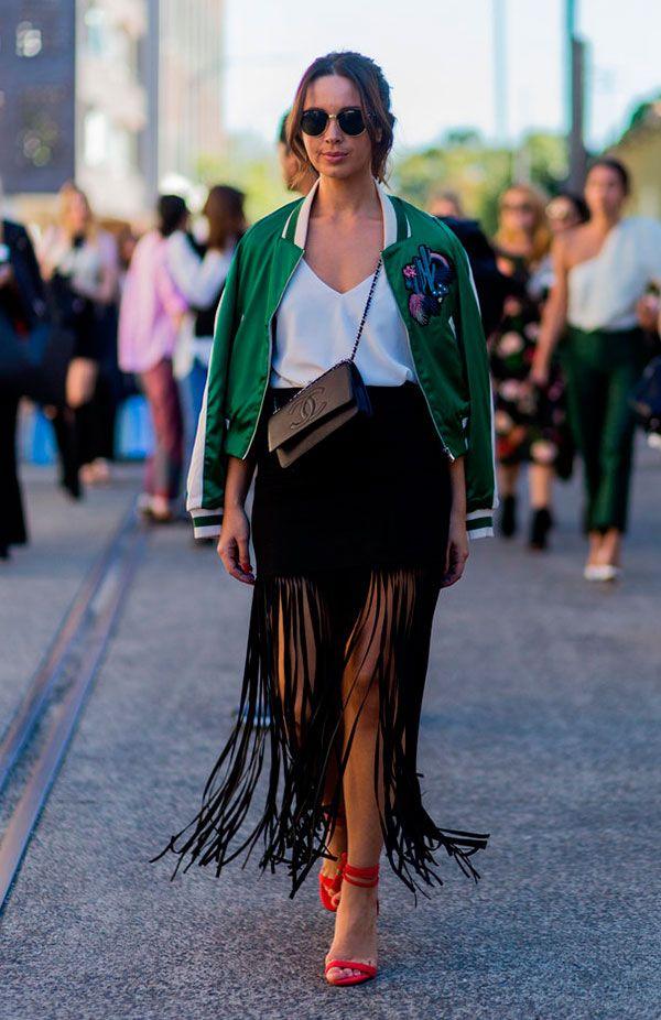 Street style look com saia midi franjas preta, regata seda, bomber jacket verde e sandália vermelha