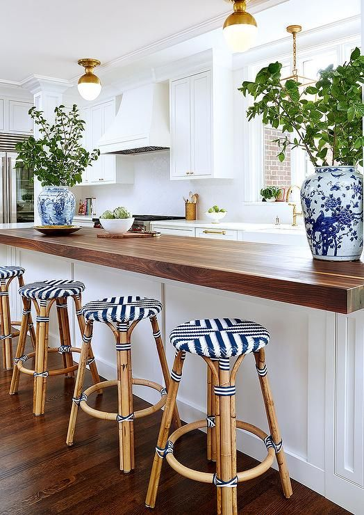 A wainscoted kitchen peninsula is topped with a thick dark stained butcher block matching hardwood floors.