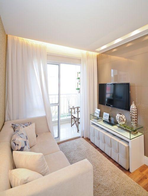 sala de estar pequena decorada com sofá branco pequeno, tapete claro, e puff embutido no rack da televisão