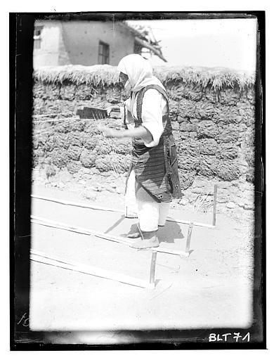 Grèce ; Macédoine ; Negocani (Νίκη-Φλώρινα)  (1916-1917) Légende Jeune femme s'occupant à préparer les fils de chaîne pour le tissage. En second plan, mur en terre battue et paille Auteur photoBlanchet, Joseph