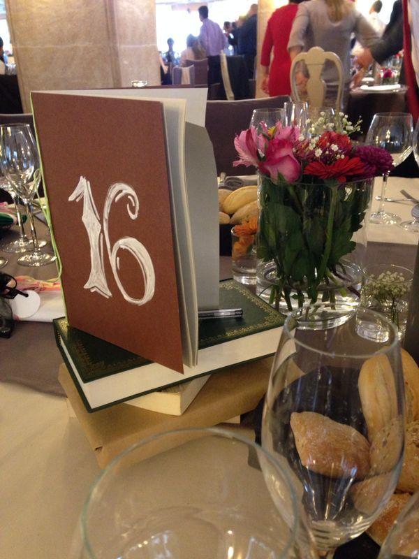 El centro de mesa es también un libro de firmas. Tiene el número de la mesa en la portada y dentro una petición de los novios donde invitan a sus familiares y amigos de la mesa a que les dejen un mensaje o anécdota del gran día.