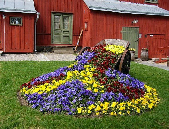 29 best front flower bed ideas images on pinterest pansies bed old wheel barrel used as a planter in the flower bed mightylinksfo