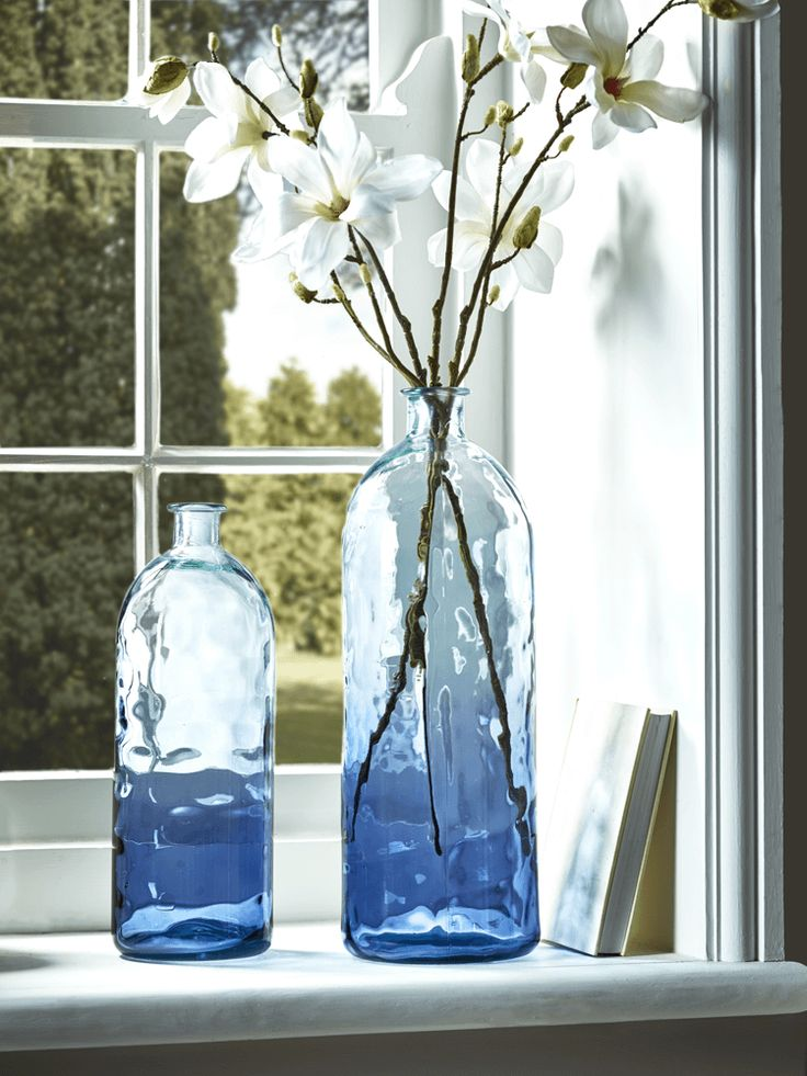 Individually handmade in Spain from coloured glass with a soft blue ombre effect, our bottle shaped vases in medium and large each have a unique rippled effect across the surface. Perfect for displaying one or two stems, or as a pair on your tabletop or mantelpiece.