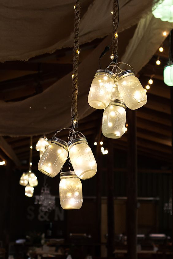 Clusters of frosted LED mason jar lights hung from the ceiling at this rustic barn wedding. So gorgeous and magical!: