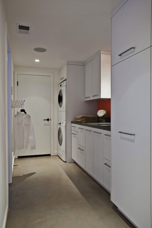 Fiorella Design - laundry/mud rooms - long laundry room, narrow laundry room, white laundry room, concrete floors, stacked washer and dryer,...