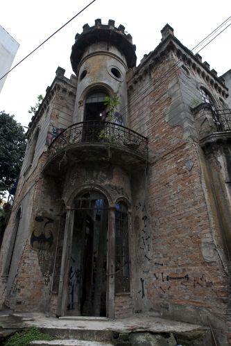 """Construído em uma esquina da Avenida São João, no centro de São Paulo, o """"Castelinho da rua Apa"""" chama a atenção por três características: sua imponência arquitetônica, sua história macabra e seu atual estado de abandono. O """"castelinho"""" foi construído em 1912 e, durante anos, serviu de residência para a rica família César dos Reis. De arquitetura eclética, a obra exibe uma torre que remete aos castelos medievais da Europa. Em maio de 1937, porém, o local se tornou cenário de uma tragédia…"""