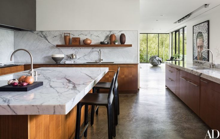 Marble countertops complement walnut-veneer cabinetry and polished concrete floors in the kitchen | archdigest.com