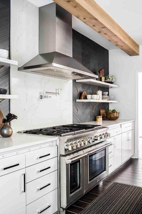 Contemporary kitchen is equipped with a Thermador dual stove placed against a white quartz slab cooktop backsplash fitted with a polished nickel swing arm pot filler mounted beneath a stainless steel vent hood.