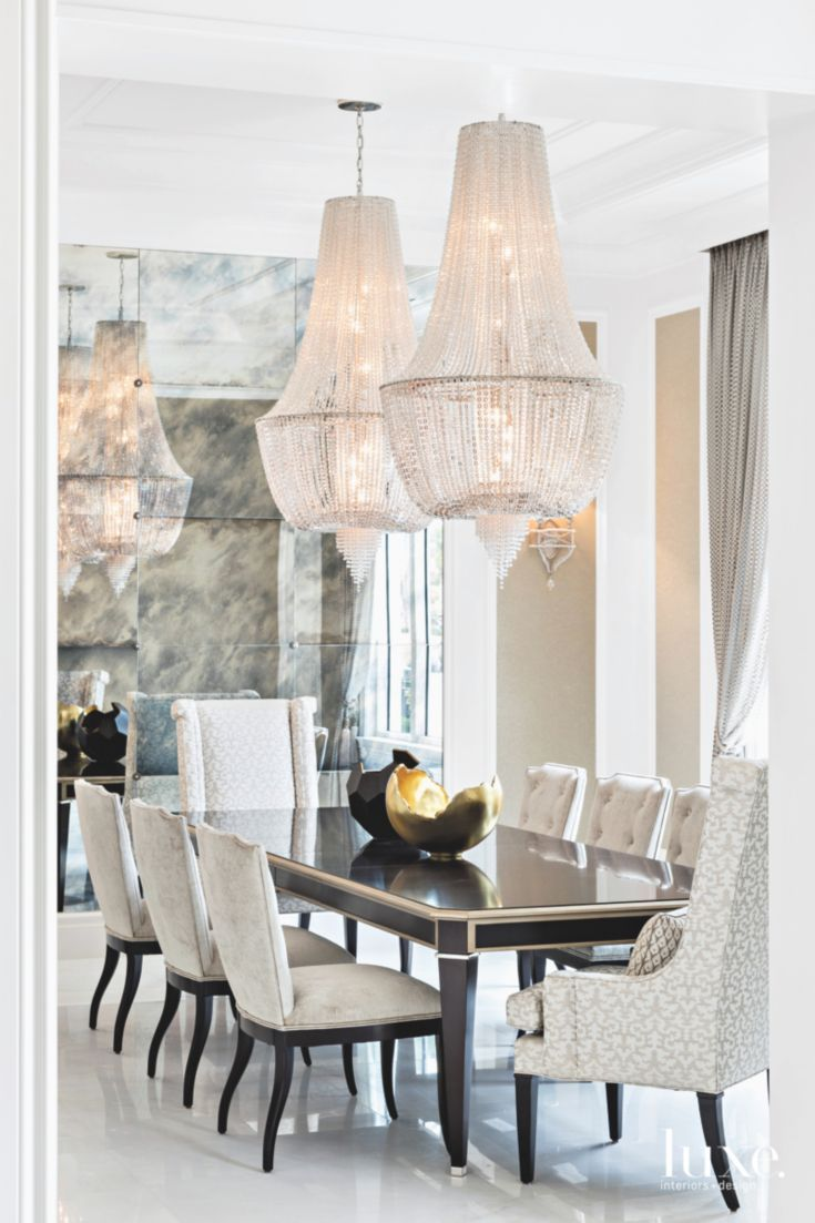 Double Dripping Chandeliers In Mirrored Formal Dining Room