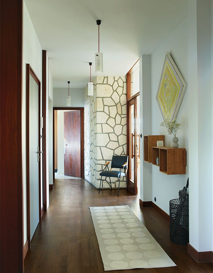 French entryway with wood shelves, pendants, a rug, and a vintage chair