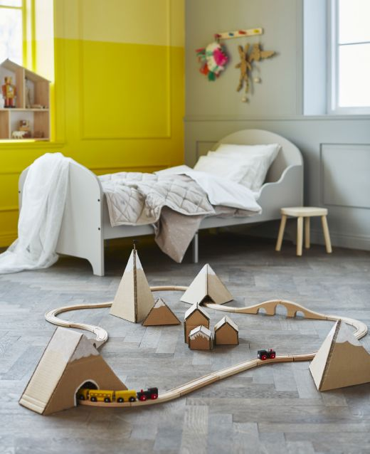 In a kids' bedroom, a toy train set rides through a mountain range made of cardboard. Other ways to reuse cardboard boxes for kids toys in the same link
