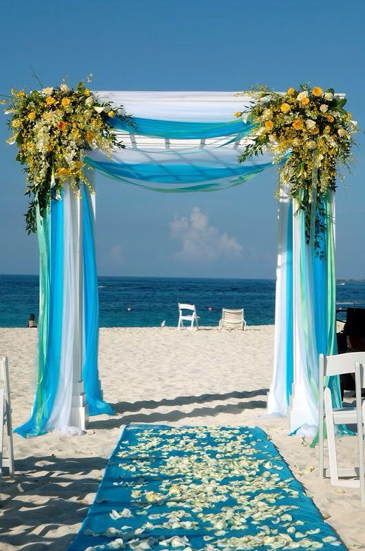 Gazebo in legno bianco in riva al mare decorato con stoffe bianche azzurre e verde acqua, Addobbato con composizioni di fiori sui toni del giallo