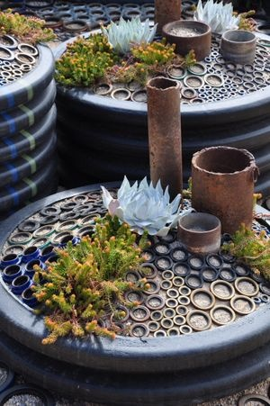 The corrugated soil containers are large, black plastic drainage pipes left over from a construction project.   All those circles around the pots and acting as a decorative mulch are pressure gaskets and seals from industry machinery