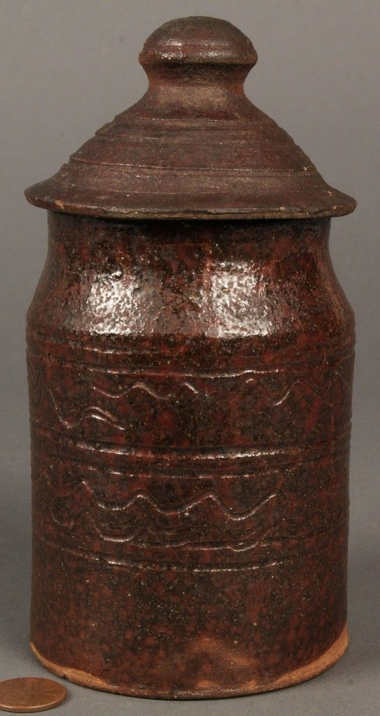 Case Antiques Auctions, 05-21-2011, $3,304. East Tennessee redware sugar jar, straight sides with quadruple sign waves and three bands of incised lines around body having steeply domed top with large mushroom finial. Made by the Mort pottery family of Jefferson County, TN.