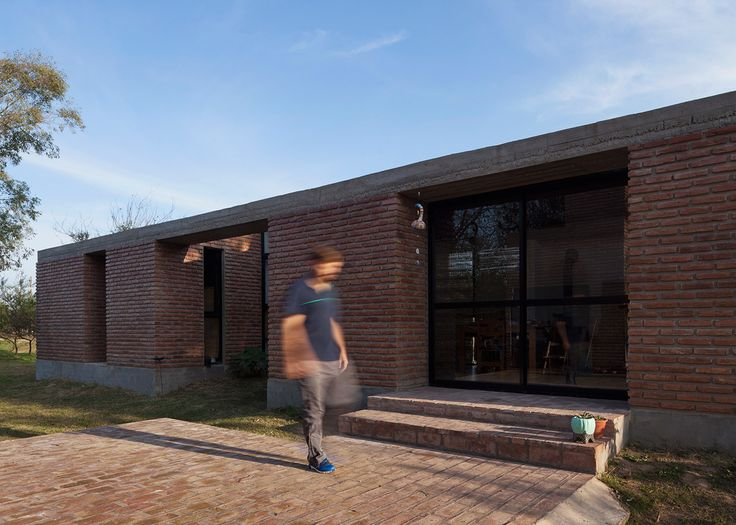 This simple brick house by architect Germán Müller features a series of large windows, offering generous views of its scenic setting in Santa Fe, Argentina