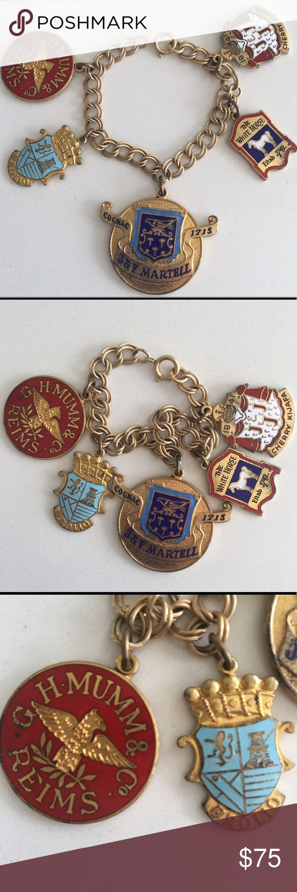 """Vintage Charm Bracelet with Liquor Labels/Shields This vintage gold toned and enamel bracelet features labels from famous European champagne & liquor brands. They include: J & F Martell Cognac, The White Horse Scotch Whisky, Cherry Kijafa liqueur, Brolio Chianti, and G.H. Mumm Champagne. A wonderful conversation piece. In overall great vintage condition with some tarnishing and scratches mostly on back side of charms. Measures approximately 6 3/4"""" long. Vintage Jewelry Bracelets"""