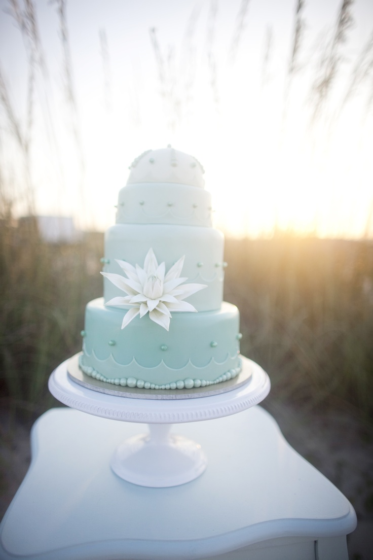 Shades of Seafoam Green and Aqua Blue, Custom Sugar Pearls and a White Sugar Cactus Bloom Adorn this Oceanside Wedding Cake. :: Photo by: millieholloman.com