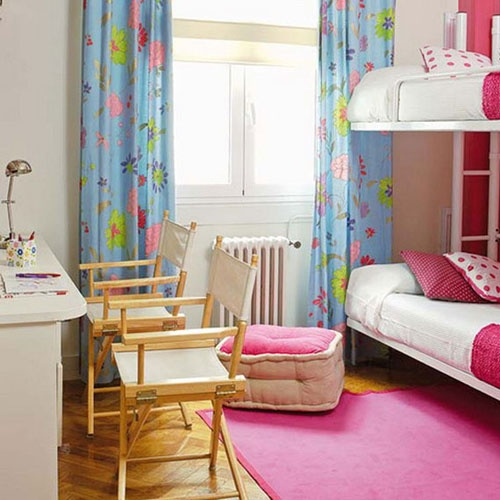 This girls room for two features bunk beds dressed in pink, which take up less space than side-by-side beds, and a desk with folding canvas chairs that can easily be folded and moved out of the way.