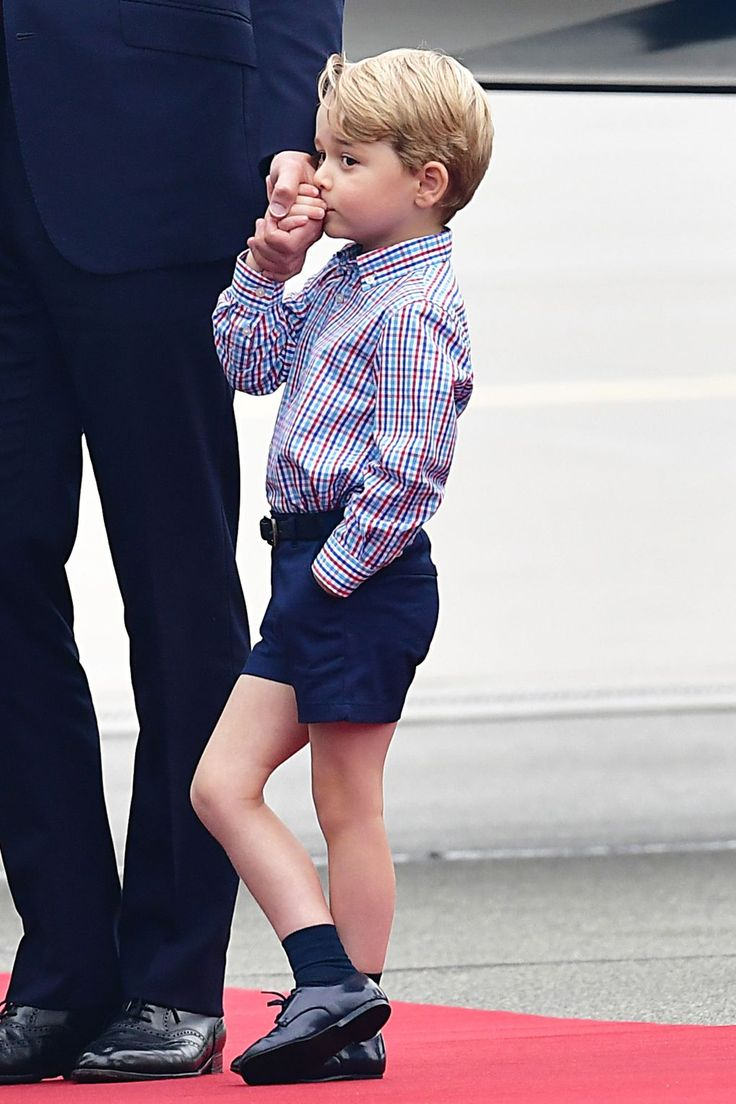 Prince George tugging at the hand of his father, Prince William.