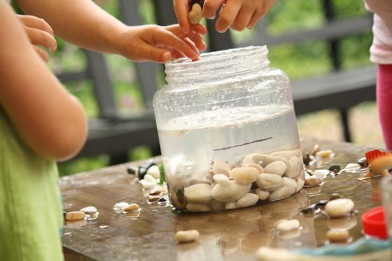 rocks and bucket of water. Water displacement activity. Dropping small round stones into jar of water, watch wat happens to the level fo water as you add rocks.