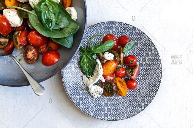 Tomato salad on plate with salad bowl, basil, mozzarella, exotic tomatoes, cherry tomatoes, salad, mediterranean, olive oil, healthy salad,